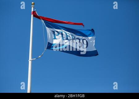 Pier 39 Flag flying in the wind against a clear blue sky - Stock Photo