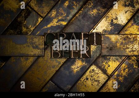 Photo of real authentic typeset letters forming Craft Beer text on vintage textured grunge copper and gold background