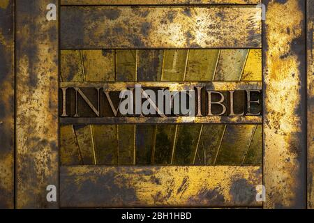 Photo of real authentic typeset letters forming Invincible text on vintage textured grunge copper and gold background