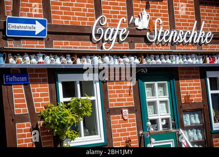 Boizenburg, Germany. 21st Apr, 2020. Coffee pots stand on a shelf on the outside wall of the café in the old town, which is closed due to corona protection measures. Due to the lack of tourists caused by the corona protection measures, the cities in Mecklenburg-Vorpommern are not very busy. After several weeks of forced closure due to the corona protection measures, many retail shops in Mecklenburg-Vorpommern have reopened. Credit: Jens Büttner/dpa-Zentralbild/ZB/dpa/Alamy Live News - Stock Photo