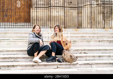 Two happy young women sitting on stairs in the city Stock Photo