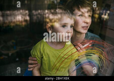 Portrait of mother and her little son looking out of window with drawn rainbow - Stock Photo