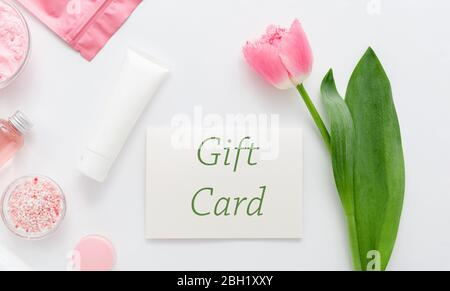 Gift card with pink flower on white background from beauty salon cosmetics perfumery shop. Gift card present coupon for woman. Surprise voucher for - Stock Photo
