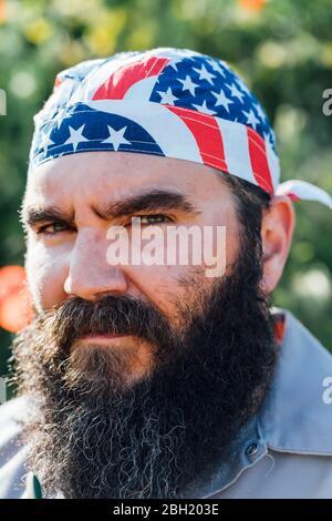 Portrait of bearded man wearing Stars and Stripes headgear - Stock Photo