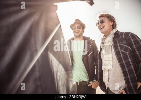 Three happy men talking in backlight - Stock Photo