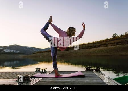 Young woman doing yoga on a jetty, dancer position - Stock Photo