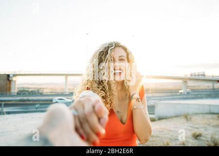Portrait of happy young woman holding hands at evening twilight