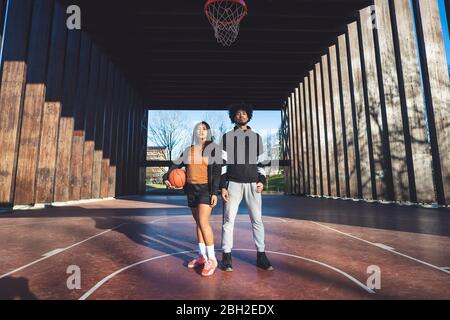 Portrait of young man and woman standing on basketball court