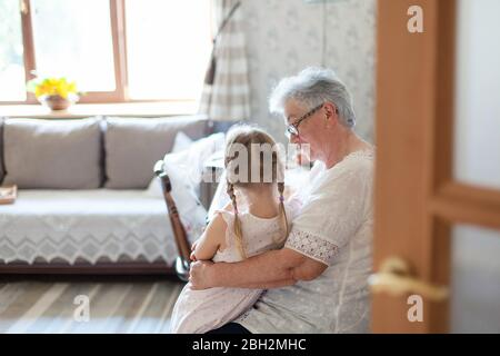 Grandmother is hugging granddaughter in cozy home living room. Kind senior woman is telling story - Stock Photo