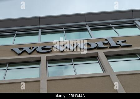 Low-angle view of logo for coworking company WeWork in the Silicon Valley, Redwood City, California, April 10, 2020. () - Stock Photo