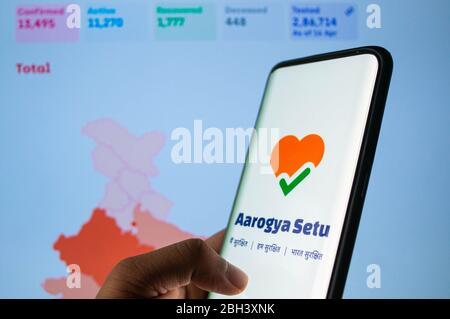 Aarogya Setu app logged in on a mobile infront of a red screen with status of coronavirus spread in India in background - Stock Photo
