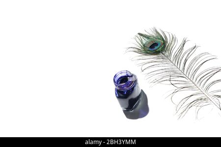 Inkwell and peacock feather on white background Stock Photo