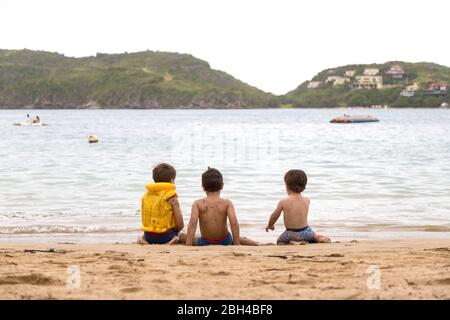 Three little brazilian children playing on the beach, next to the water, in ferradura beach in buzios brazil. Real people. Stock Photo
