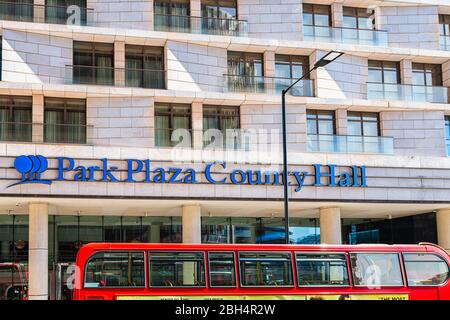 London, UK - June 22, 2018: Blue sign for park plaza County Hall hotel on exterior of building on street and red bus - Stock Photo