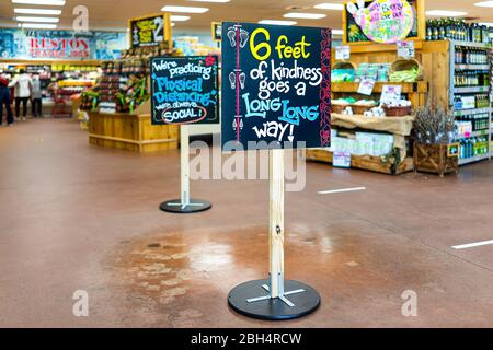 Reston, USA - April 9, 2020: Social distancing sign inside Trader Joe's grocery shop store during coronavirus with empty interior - Stock Photo