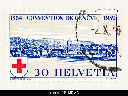 SEATTLE WASHINGTON - April 18, 2020:  Blue Swiss postage stamp with view of Geneva, commemorating 75th anniversary of International Red Cross Society. - Stock Photo