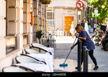 London, UK - June 26, 2018: People woman employee restaurant worker cleaning street road in center of downtown city mopping wet floor ground pavement