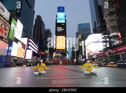 New York, United States. 23rd Apr, 2020. Two girls record themselves doing yoga in Times square Coronavirus are displayed in Times Square on Thursday, April 23, 2020. New York City remains the U.S. epicenter of the Coronavirus pandemic with roughly 20 percent of the nation's cases and fatalities. Photo by John Angelillo/UPI Credit: UPI/Alamy Live News - Stock Photo