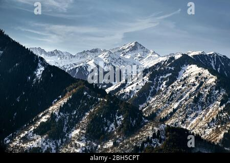 High mountains with snow and pine trees and peak against blue sky in Kazakhstan at winter time