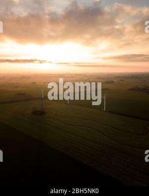 aerial landscape view of fields in the sunset with big white windmills on - Stock Photo