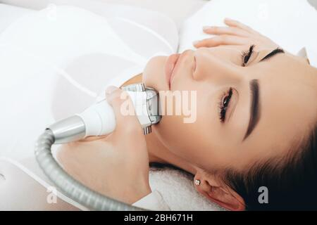Using the LPG apparatus, the beautician performs a face lift massage. Face contour lift, close-up - Stock Photo