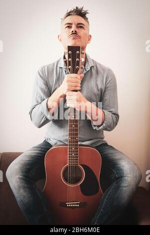 Handsome man in casual clothes is posing with his acoustic guitar. Guy with guitar sitting on sofa in living room. Attractive man holding guitar in hi