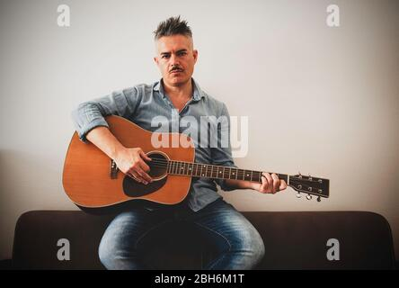 Handsome man in casual clothes is posing with his acoustic guitar. Guy playing guitar sitting on sofa in living room. Attractive man holding guitar in