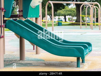 empty green double slide and other playground equipment blocked by yellow caution tape during covid-19 lock down - Stock Photo