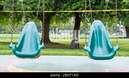 two empty green plastic playground swings in a large park blocked by yellow caution tape due to covid-19 lock down - Stock Photo