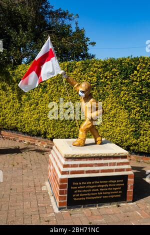 """Carved, wooden """"Clockpelters"""" statue wearing medical mask during the Covid-19 pandemic, on St Georges Day with an England flag. Great gonerby, Grantha - Stock Photo"""