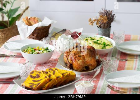 Homemade holiday dinner with baked chicken, mashed potatoes, salad, snacks and dessert.