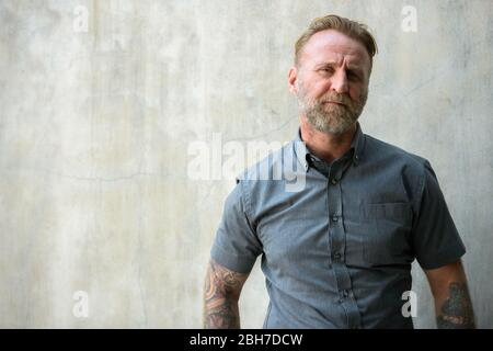 Mature rebellious bearded man with hand tattoos outdoors - Stock Photo