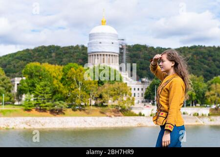 Charleston, West Virginia capital city with woman looking at scaffold construction on state capitol dome from university grounds by river - Stock Photo