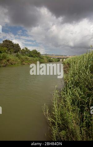 Brownsville, Texas  October 7, 2009:  The Rio Grande River flowing through downtown Brownsville, looking west with Matamoros,  Mexico on the left.  The border wall is being built in sections along some parts of the river where smuggling is prevalent. © Bob Daemmrich