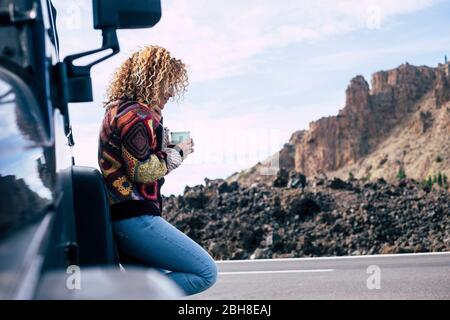 beautiful independent curly blonde middle age caucasian woman rest after a travel with her off road black car parked near the street. Mountains and sky in background for adeventure concept and alternative vacation