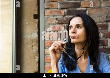 Close-up of thoughtful mature woman with eyeglasses looking through window at cafe