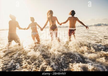Defocused for active and motion concept people have fun running in the sea water during summer vacation - group friends together enjoy happiness - action caucasian men and women in friendship - Stock Photo