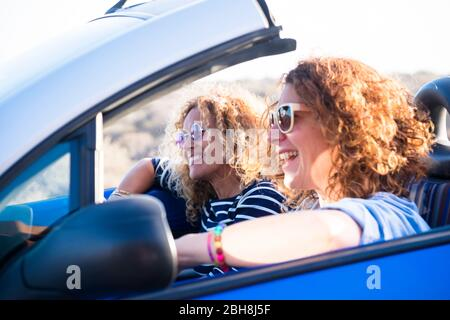Couple of curly cheerful woman smiling and having fun together enjoying the travel vacation driving the car - people on the move in convertible vehicle in sunny day of summer - Stock Photo