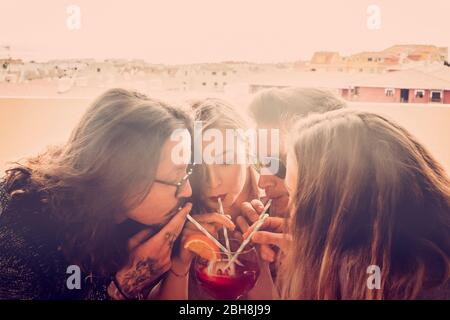 Group of friends two couples men and women celebrate and have fun together drinking from the same glass - party event time in friendship for caucasian people - new year outdoor celebration - Stock Photo