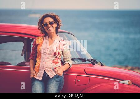 Beautiful caucasian middle age lady driver pose standing with a red legendary retro vintage car behind - ocean in background for travel and alternative lifesyle concept - Stock Photo