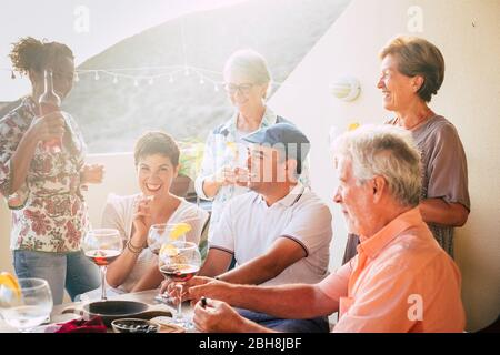 Cheerful different ages people stay together for lunch and drinking wine having a lot of fun - group of caucasian people laughing - mature adult and young - sunny backlight in outdoor terrace - food and drinks - Stock Photo