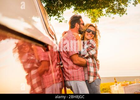 Love and married lifestyle concept for beautiful caucasian couple of traveler hugging and kissing with red vintage van - mirror and cheerful happy people enjoying the outdoor leisure activity together