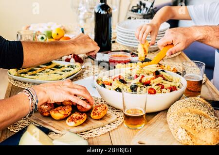Group of caucasian friends enjoying together a happy lunch with italian meat lke pasta and pizza - beer and wine to have joy in friendship - wood table - home restaurant concept - Stock Photo