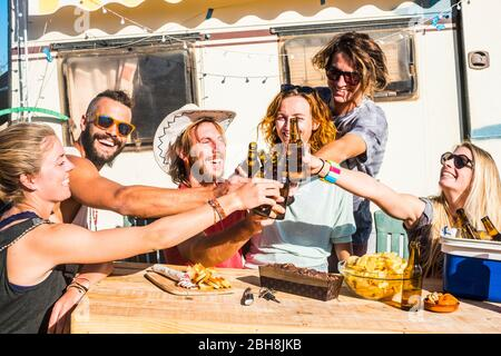 Group of happy friends tosting and clinking together beer with happiness - nice people with nature and outdoor lifestyle - boys and girls smiling and laughing with alternative caravan in background - Stock Photo