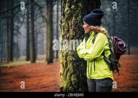 Lonely caucasian middle age woman standing in the forest and look the beautiful wood around her - concept of alternative trekking vacation in wild outdoor - backpacker and traveler people