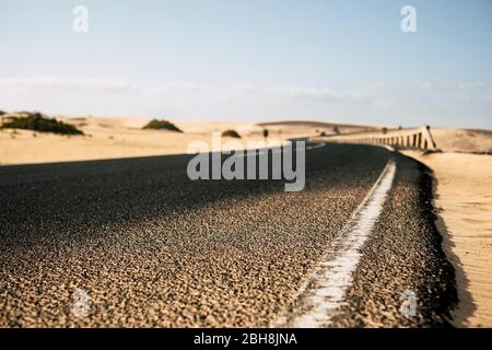 Ground close up point of view of black asphalt long road with desert sand dunes on the sides - travel and explore destination alternative summer holiday concept - focus on the first part and defocused backgorund