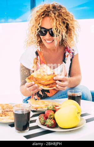 Beautiful cheerful curly long blonde hair woman eating italian pizza outdoor in restaurant or home terrace - trendy young female with tatoo and casual coloured style - Stock Photo