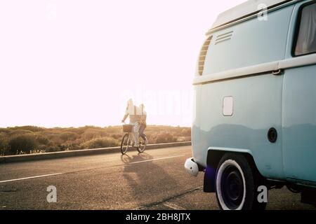 Nice happy crazy youthful concept couple enjoy riding together ona same bike like young - no limit age people play on the road with sunset in background and old vintage blue van parked - happiness joyful concept for retired couple Stock Photo
