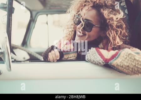 Cheerful happy beautiful caucasian young woman looking and smiling out of the window from old vintage van bus with sunglasses - travel driving concept for cute attractive girl with curly hair - Stock Photo