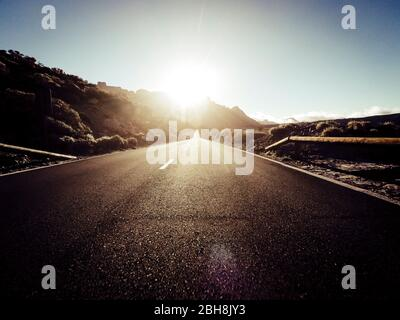 Long way road at the mountain with sun in front and sunlight effect - ground point of view with black asphalt and white lines - driving and travel concept